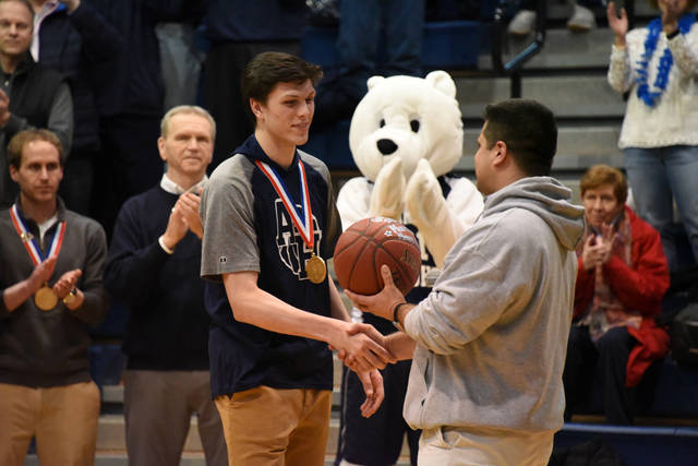 Abington Heights High School Principal Andrew Snyder, right, presents junior George Tinsley with a basketball commemorating his 1,000th career high school point during a Night of Champions April 4.