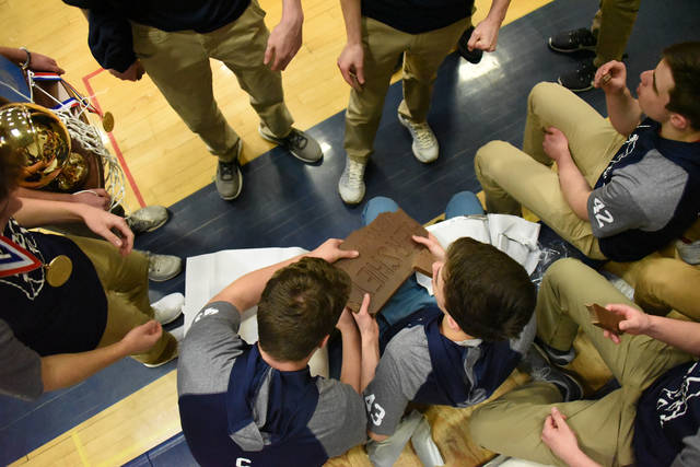 Members of the Abington Heights boys basketball team, PIAA Class 5A champs, break into a Hershey's chocolate bar during a Night of Champions April 4 at the high school.