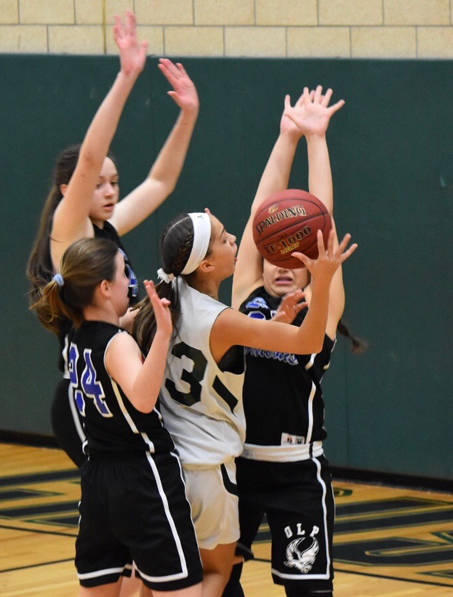 OLP's Anna Kosierowski, Angelesa DeNaples and Stephanie Yatko block a shot attempted by an All Saints player.