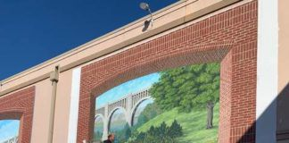 Bob Lizza works on the secondmural panel in the 'Telling Wyoming County History Project' at the Dietrich Theater. The mural can be viewed from the by-pass or in the theater's parking lot.