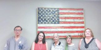 Council members stand in front of an American flag of wooden slats made by Emergency Management Agency director Artie Frank. From left are Frank, code enforcement officer Jen Basalyga, council president Gerrie Carey, treasurer Sarah Lodwick, and borough manager Virginia Kehoe.                                  Ben Freda   For Abingotn Journal