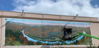 Bob Lizza puts the finishing touches on the mural that he just installed of the Vosburg Neck of the Susquehanna River, which is the third and final mural of the Dietrich Theater's Telling Wyoming County's History Mural Project.                                  Submitted photo